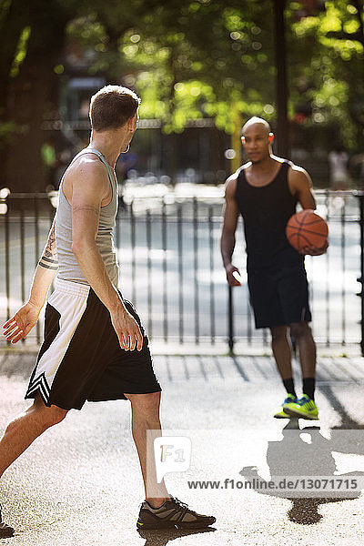 Friends practicing basketball in court on sunny day