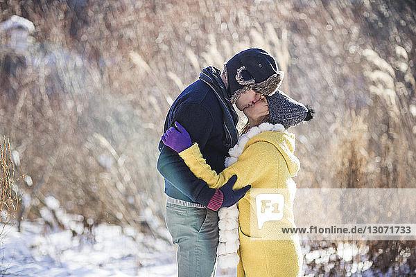 Seitenansicht eines Paares  das sich küsst  während es auf einem schneebedeckten Feld steht