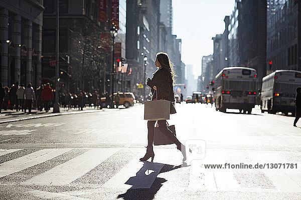 Seitenansicht einer Frau  die in der Stadt die Straße überquert
