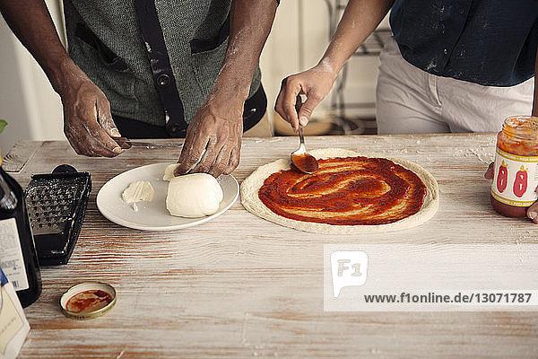 Mittelteil eines Paares beim Pizza-Backen am Küchentisch