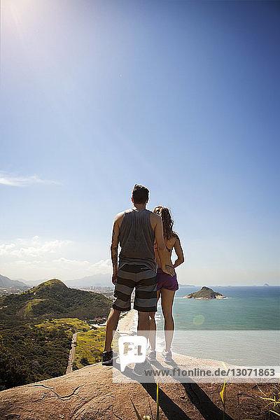 Rückansicht eines Paares  das auf einem Felsen steht und die Aussicht betrachtet