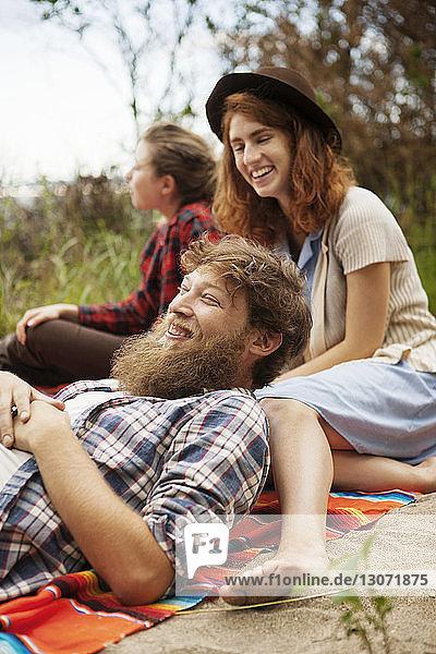 Lächelnde Freunde entspannen sich auf dem Feld