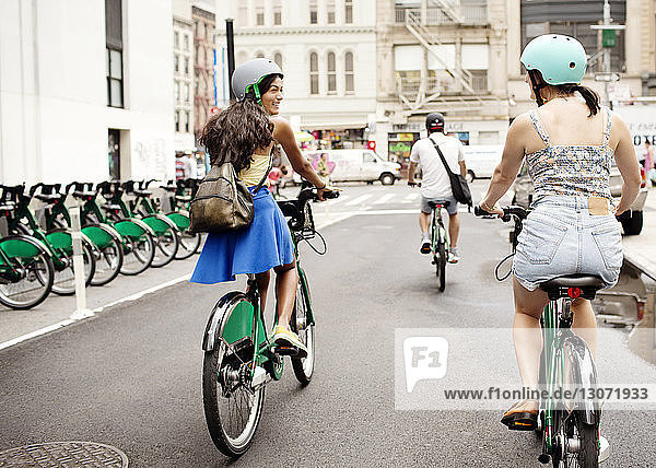 Friends riding bicycle on city street