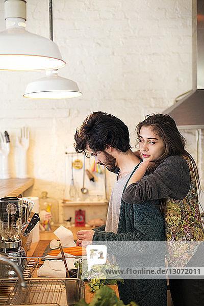 Frau lehnt sich in der Küche an Mann an