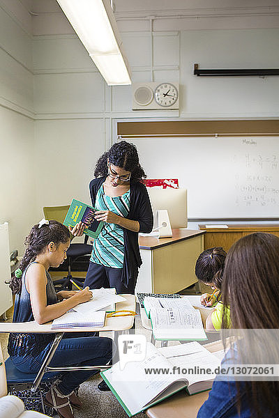 Teacher looking at student while teaching in classroom
