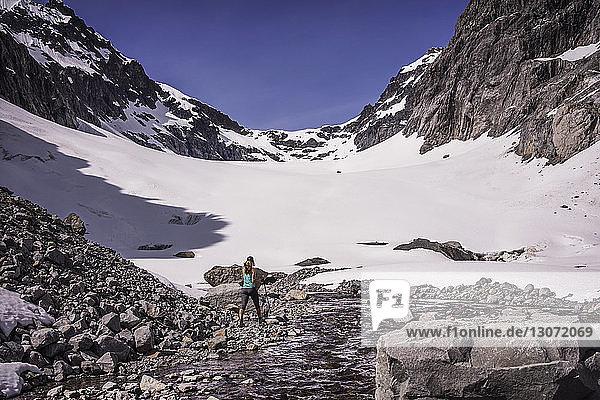 Rückansicht einer Frau  die auf einem schneebedeckten Berg wandert