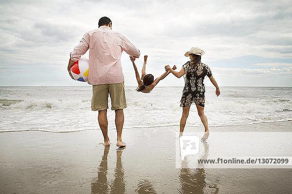 Rückansicht von spielerischen Eltern  die ihre Tochter am Strand aussuchen