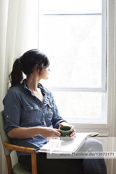 Frau mit Tasse und Buch  die wegschaut  während sie zu Hause auf einem Stuhl am Fenster sitzt