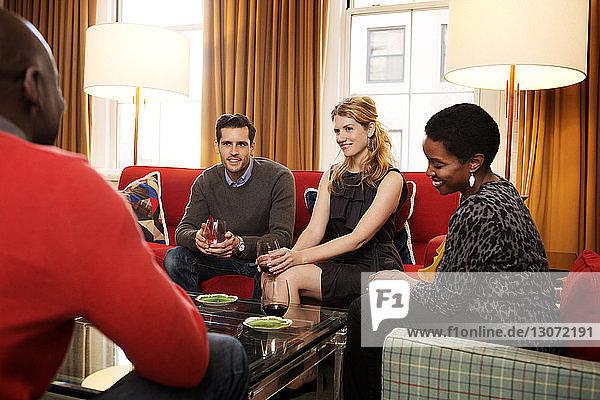 Freunde unterhalten sich  während sie zu Hause auf dem Sofa mit Weinglas sitzen