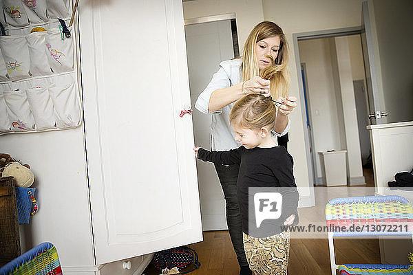 Mutter bindet der Tochter die Haare  während sie zu Hause steht
