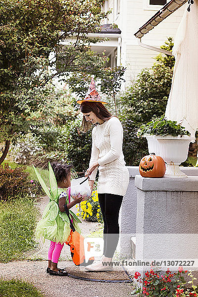 Woman giving candies to girl in Halloween costume during trick or treating