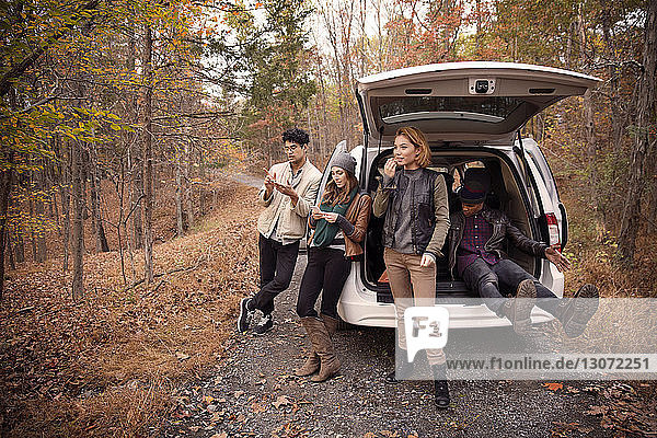 Friends relaxing by car on road amidst trees at forest during winter