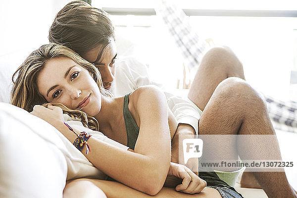 Porträt einer Frau  die zu Hause mit einem Mann auf dem Sofa sitzt