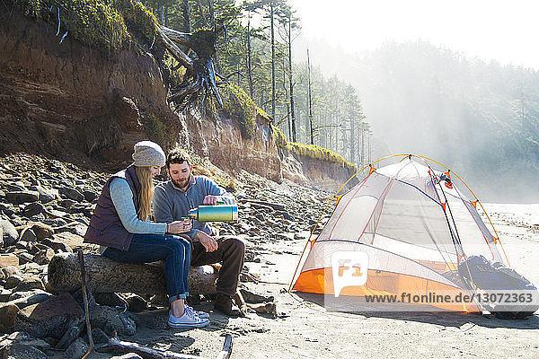 Mann schenkt Frau ein Getränk ein,  während er am Strand auf Holz sitzt