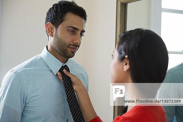 Woman adjusting man's necktie at home