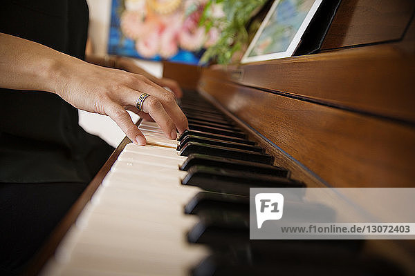 Cropped image of woman's hands playing piano at home