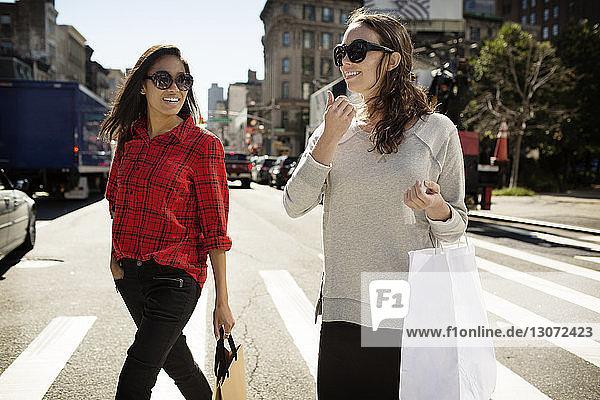 Frau mit Einkaufstaschen überquert Straße in der Stadt