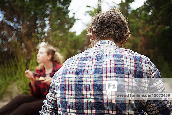 Rear view of man sitting with friend in forest