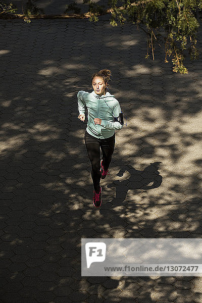 High angle view of woman jogging on road in park