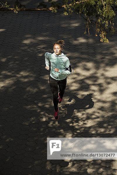 Hochwinkelaufnahme einer Frau  die auf einer Straße im Park joggt