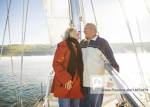 Glückliches älteres Ehepaar,  das im Sommer auf einer Yacht auf See steht