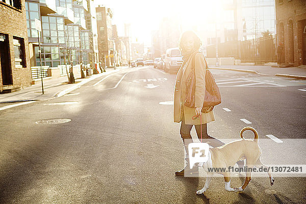 Side view of woman with dog crossing road in city