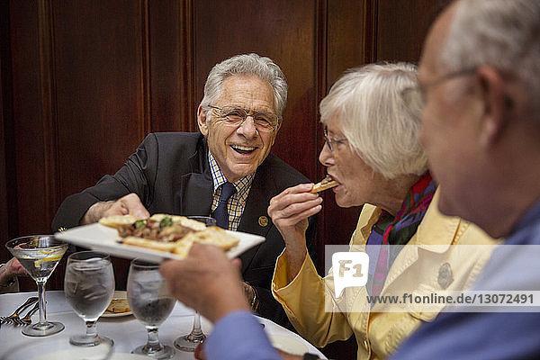 Freunde essen Essen  während sie im Restaurant sitzen