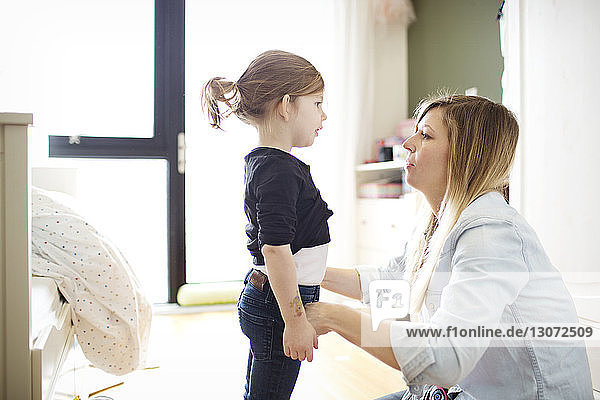 Seitenansicht einer Frau  die ihre Tochter zu Hause anzieht