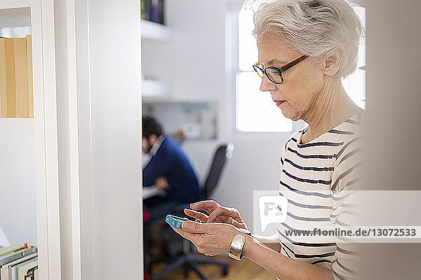 Woman using smart phone while son sitting on chair at home