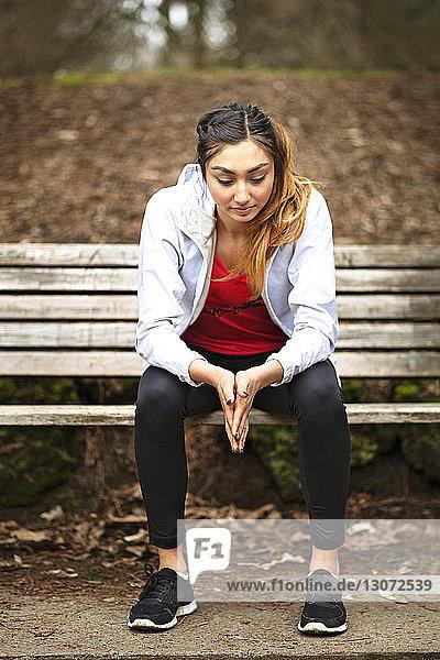 Nachdenkliche Frau sitzt auf Parkbank