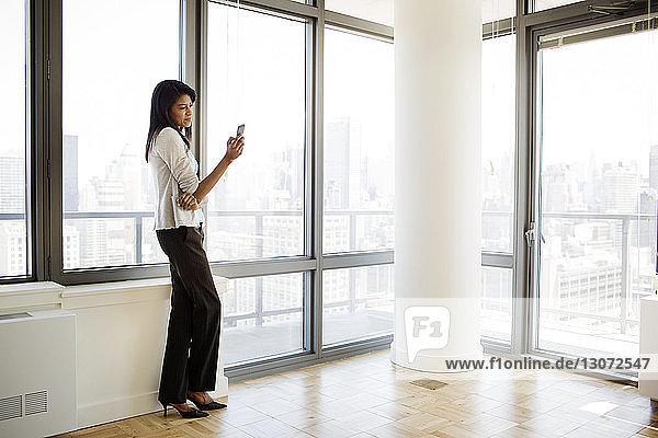 Geschäftsfrau benutzt Mobiltelefon  während sie im Büro am Fenster steht