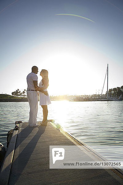 Couple standing on pier against clear sky