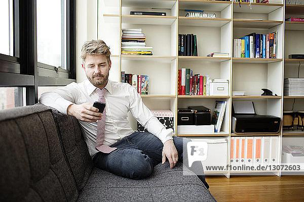Mann benutzt Mobiltelefon  während er zu Hause auf dem Sofa sitzt