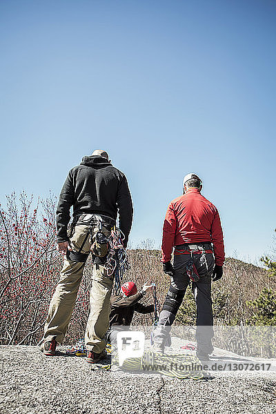 Rear view of hikers looking at man rappelling while standing against clear sky