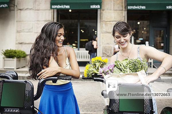 Frau sieht Freund an und legt Blumen in Fahrradkorb