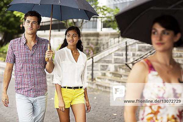 Friends carrying umbrella while walking on footpath in city