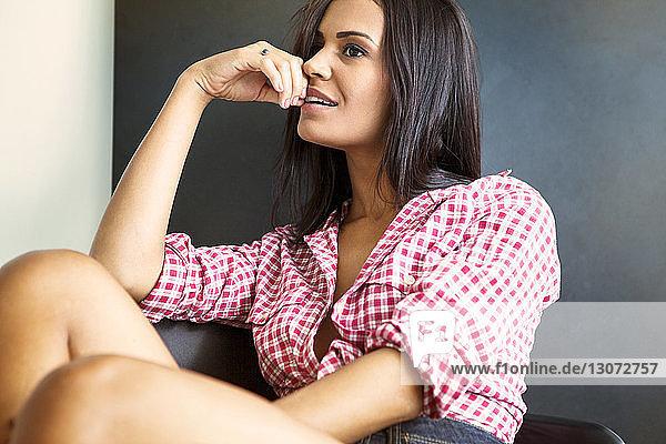 Verführerische Frau schaut weg  während sie zu Hause auf einem Stuhl sitzt