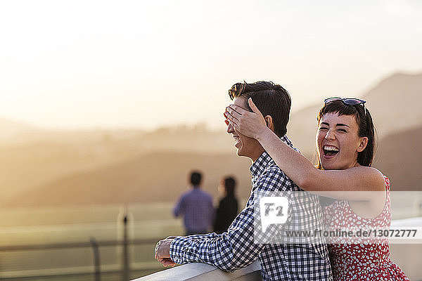 Cheerful couple standing at observation point