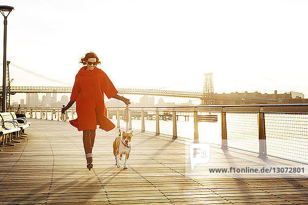 Woman with dog running on promenade against Williamsburg Bridge