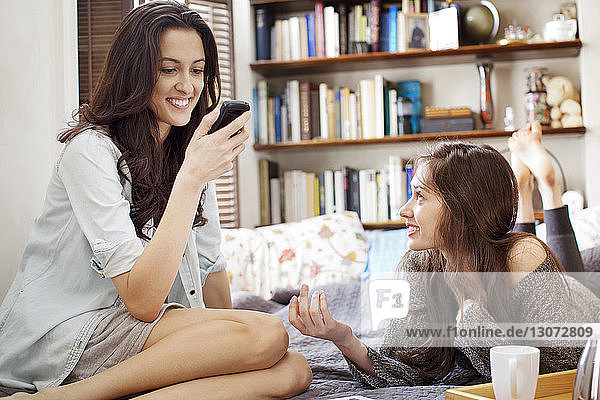 Woman looking at sister using mobile phone on bed