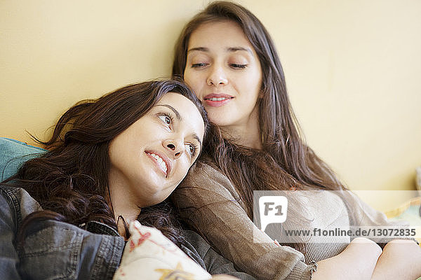 Sisters relaxing on bed at home