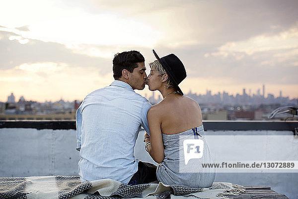 Rückansicht eines Paares  das sich küsst  während es bei Sonnenuntergang auf der Gebäudeterrasse sitzt