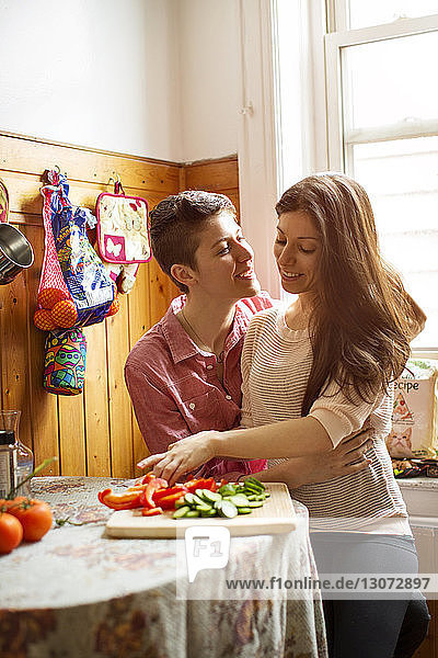 Affectionate lesbian couple preparing food in kitchen