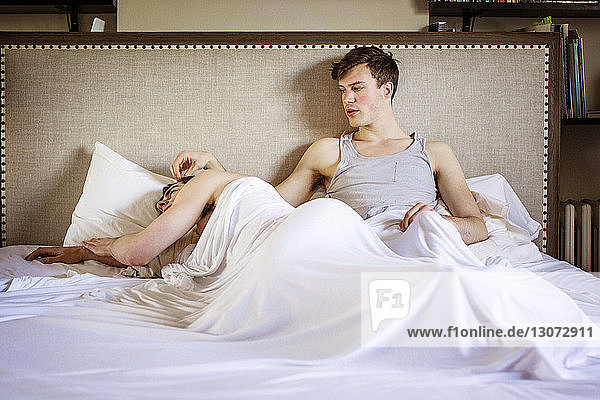 Schwuler Mann sieht Freund an  während er zu Hause im Bett liegt