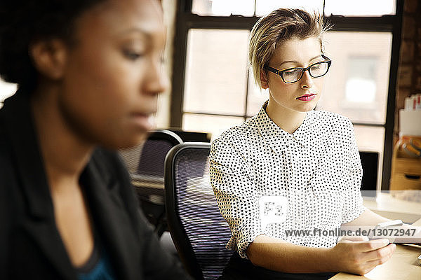 Businesswoman using smart phone while working with colleague in office