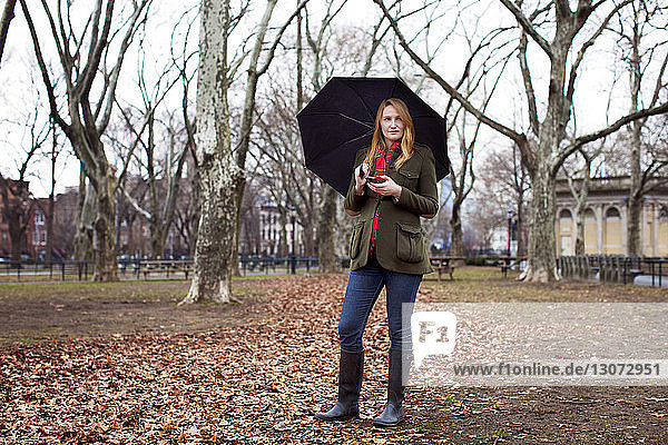 Woman with umbrella looking away while holding mobile phone at park