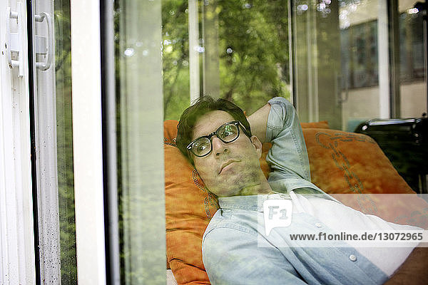 Thoughtful man wearing eyeglasses looking through window while resting at home