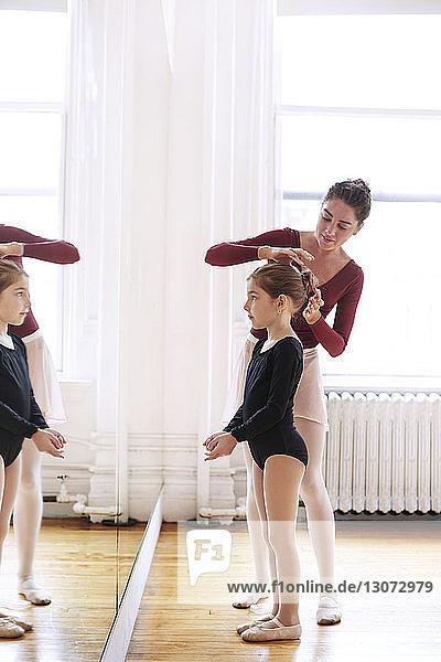 Lehrer  der im Atelier den Haarknoten einer Ballerina macht