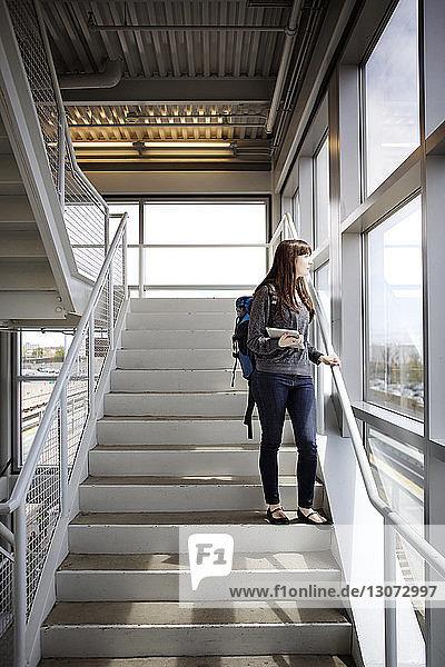 Frau mit Tablet-Computer schaut weg  während sie auf einer Treppe am Bahnhof steht