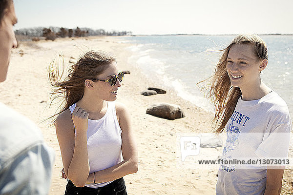 Freunde unterhalten sich  während sie am Strand an der Küste stehen